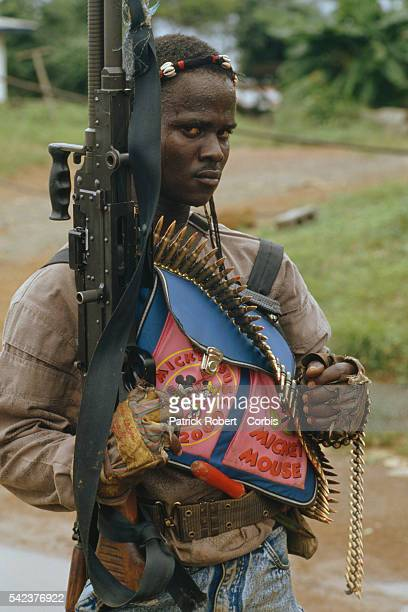 A member of the National Patriotic Front of Liberia carries a Mickey Mouse schoolbag along with his machine gun Responding to years of government...