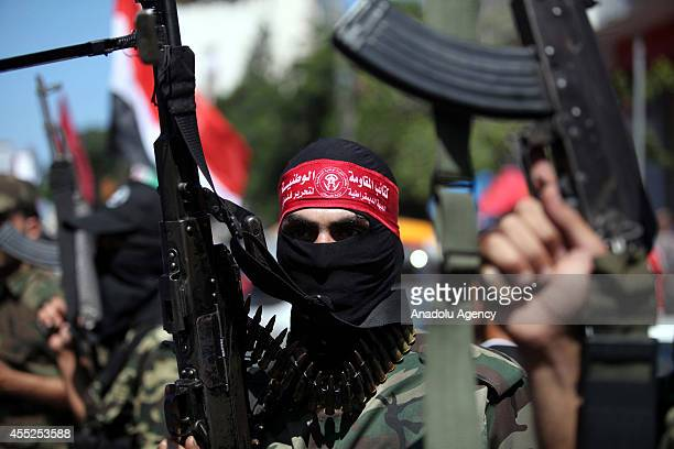 A member of the National Resistance Brigades the armed wing of the Democratic Front for the Liberation of Palestine holds a rifle during a march for...