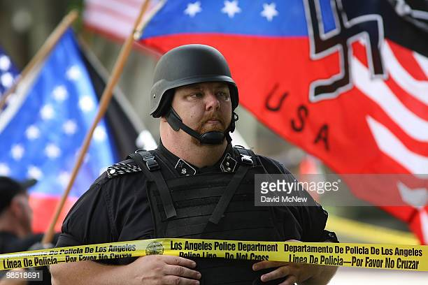 A member of the National Socialist Movement stands behind a Los Angeles police tape line during a rally near City Hall on April 17 2010 in Los...