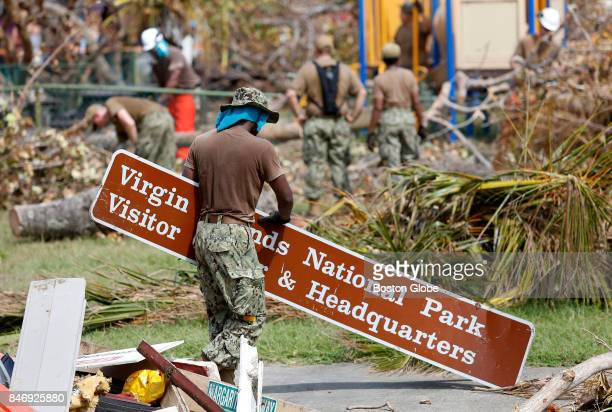 A member of the Navy clears away a sign that was knocked down in Hurricane Irma as cleanup gets underway in Cruz Bay St John in the US Virgin Islands...