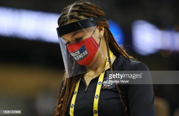 Member of the NCAA cleaning crew wears a mask and a face shield during the game of Eastern Washington Eagles v Kansas Jayhawks in the first round...
