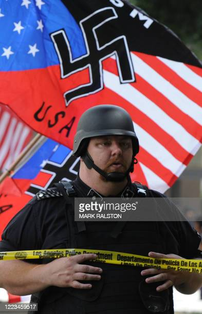 A member of the NeoNazi group The American National Socialist Movement watches an angry crowd of counterprotesters as the group held a rally in front...