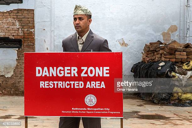 A member of the Nepali security forces stands behind a sign of a restricted area in Basantapur Durbar Square on June 24 2015 in Kathmandu Nepal...