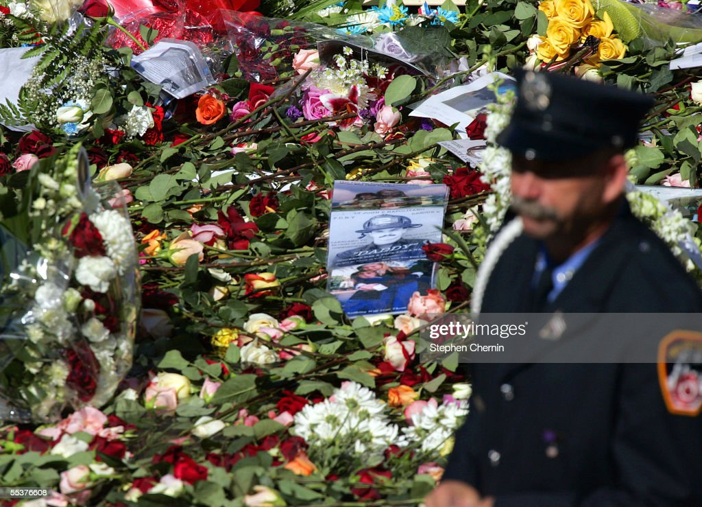 A member of the New York City Fire Department walks by the reflecting pool overflowing with flowers and images of the deceased in the footprint of the North tower September 11, 2005 in New York City. This is the fourth anniversary of the September 11th attacks.