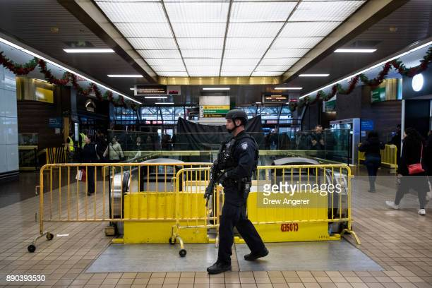 A member of the New York City Police Department stands guard inside the New York Port Authority Bus Terminal after it reopened following an explosion...