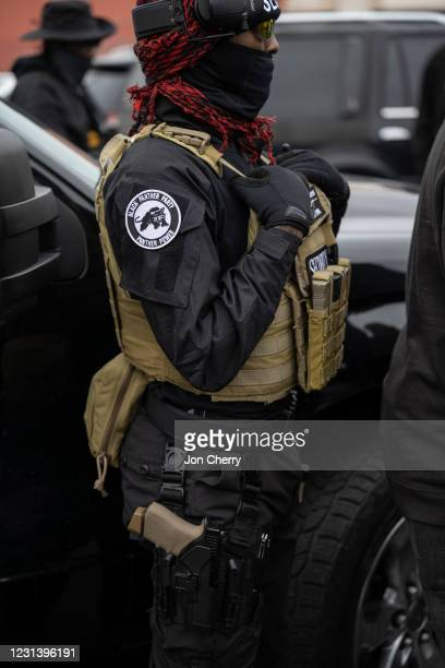 Member of the NFAC sporting a Black Panther Party patch, stands guard as Grandmaster Jay speaks with NFAC members in the Old Louisville neighborhood...