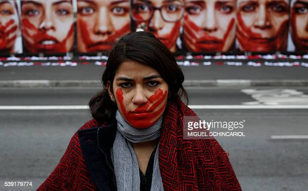 Member of the NGO Rio de Paz poses during an exhibit demonstration against violence against women, displaying some 420 panties and portraits of...