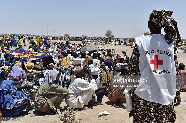 A member of the Niger's Red Cross stands next to people after the International Red Cross Committee distributed food to people who were evacuated...
