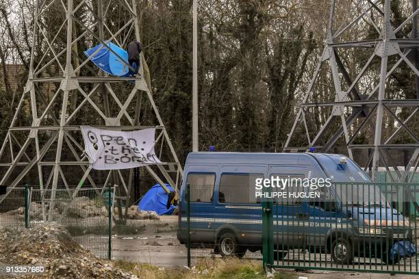 A member of the No Border network comes down of an electric pole after installing a tent in Calais on February 2 a day after a giant brawl between...