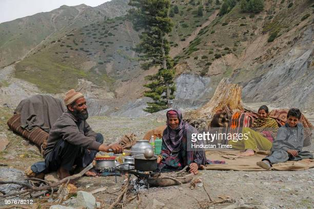 A member of the nomad Bakerwal community prepares tea as others rest in the mountains enroute to the Mughal Road some 80 kms south of Srinagar on May...