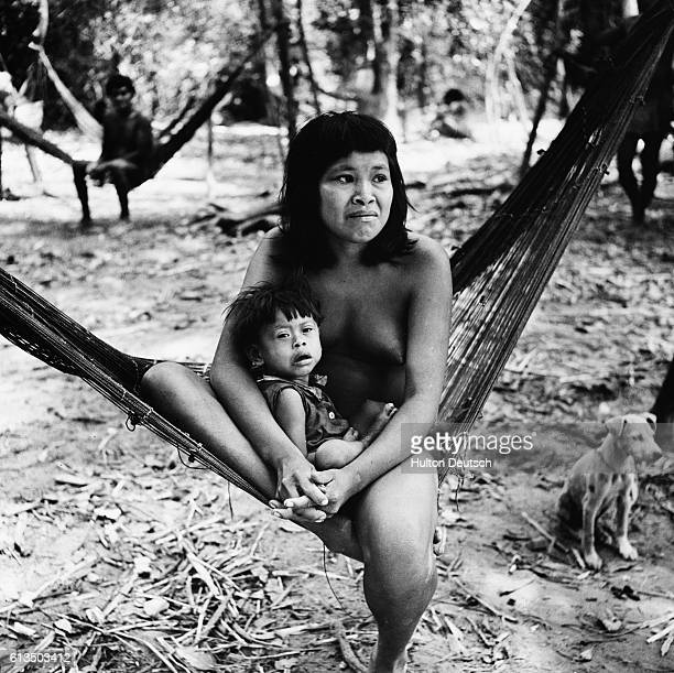 A member of the nomadic Guajibos tribe which inhabits the area around the junction of the Sinaruco and Orinoco rivers sits with her child in a...