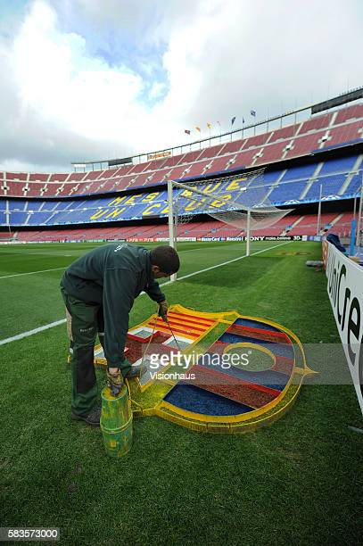A member of the Nou Camp groundstaff sprays paint on the club crest stenciled on to the grass before the UEFA Champions League Round of Sixteen 2nd...