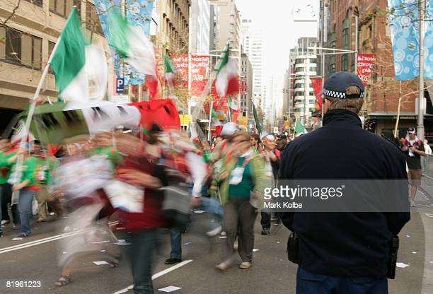 A member of the NSW Police Force watches as the Pilgrim Crowd walk down George street ahead of the Papal Welcome Ceremony for The Holy Father Pope...