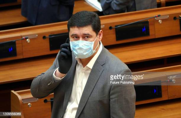 Member of the Odesa Regional Council wears a medical mask and dispensable gloves while speaking on the phone during the extraordinary session on the...