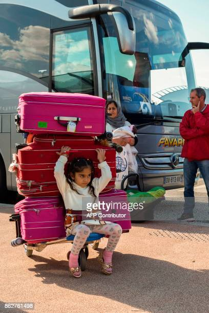 A member of the Office francais de l'Immigration et de l'Integration looks on as a migrant girl a woman and a baby wait to board a bus after landing...