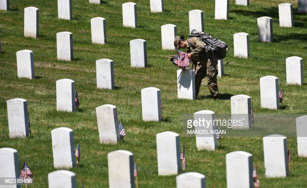 A member of the Old Guard places US flags on graves at Arlington National Cemetery on May 24 2018 ahead of Memorial Day in Arlington Virginia