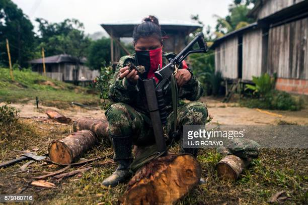 TOPSHOT A member of the 'Omar Gomez' Western War Front of the National Liberation Army guerrilla cleans her gun in a camp on the banks of the San...