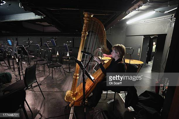 A member of the orchestra at Glyndebourne opera house tunes her instruments before a production of the Benjamin Britten opera 'Billy Budd' on August...