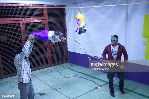 A member of the organization Deportados Unidos en la Lucha Deportees United in the Struggle hits a pinata with the figure of US President Donald...