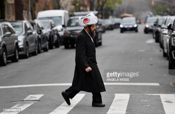A member of the Orthodox Jewish community crosses the street on April 8 2020 in Brooklyn New York as the Passover holiday starts Wednesday evening...
