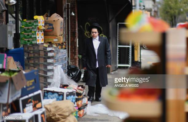 A member of the Orthodox Jewish community passes by a grocery store on April 8 2020 in Brooklyn New York as the Passover holiday starts Wednesday...