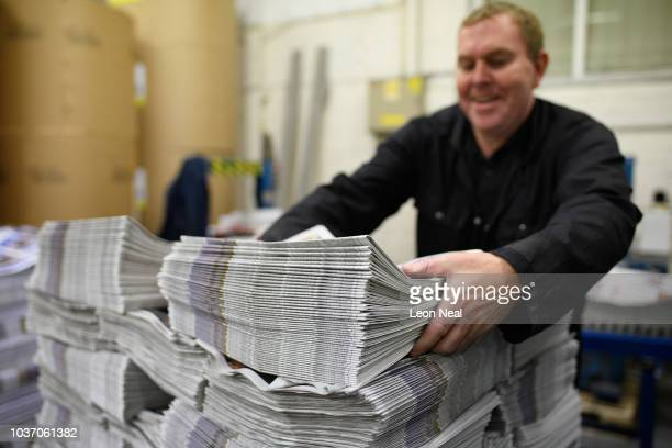 A member of the packing team stacks copies of the weekly newspaper as the latest edition is printed at the Barnsley Chronicle press during a...