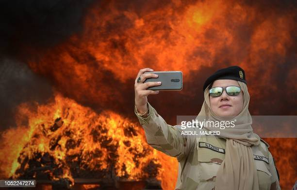 A member of the Pakistani AntiNarcotic Force takes a selfie beside a pile of burning drugs and liquor during a ceremony at the Kacha Ghari army...