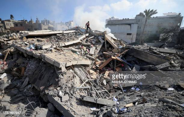 Member of the Palestinian civil defence walks amidst the rubble of a building in Gaza city which housed the Intaj Bank linked to the Hamas movement...