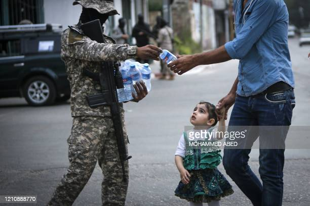 A member of the Palestinian Islamic Jihad hands out water bottles ahead of the breaking of the fast during the Islamic holy month of Ramadan in Gaza...