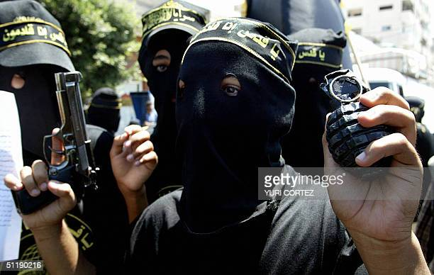 Member of the Palestinian Islamic Jihad movement holds up a grenade and gun during a demonstration in support of a hunger strike held by Palestinian...