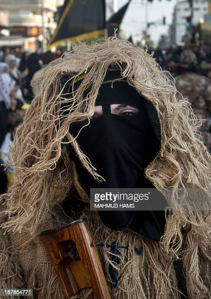 Member of the Palestinian Islamic Jihad movement parades with a gun on November 13, 2013 in the streets of Gaza City during an anti-Israel march as...
