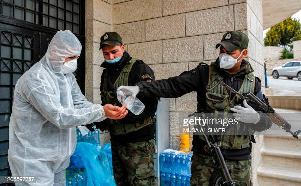 Member of the Palestinian security forces has antiseptic gel applied to his hands while being assisted to wear a protective suit before delivering...