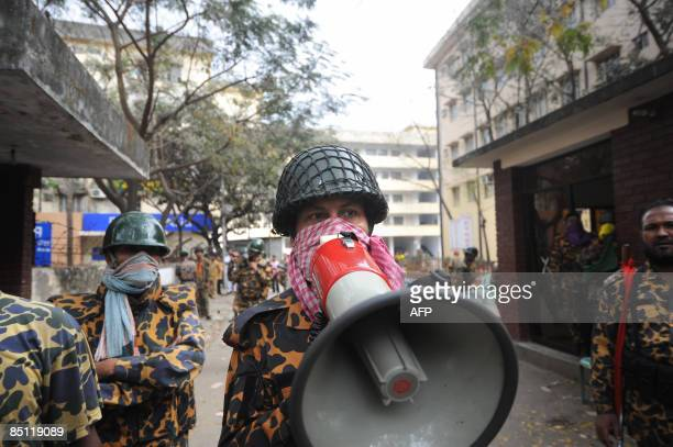 A member of the paramilitary Bangladesh Rifles troop uses a megaphone to speak from their headquarters complex in Dhaka on February 26 2009 the day...