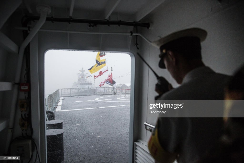 A member of the People's Liberation Army (PLA) Navy holding a a two-way radio stands onboard a ship during an open day at the Ngong Suen Chau Barracks in Hong Kong, China, on Saturday, July 8, 2017. China's bid to display some soft power in Hong Kong-- with a visit by the country's first aircraft carrier -- has also showcased its heavy-handed approach to security. Photographer: Billy H.C. Kwok/Bloomberg via Getty Images