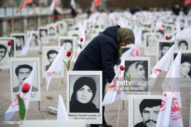 A member of the People's Mujahedin of Iran in France displays portraits of victims on the Esplanade des Invalides in Paris on October 29 2019 to...