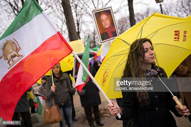 A member of the People's Mujahedin of Iran waves the former Iranian flag during a protest in Paris on December 28 2013 to condemn an attack on Camp...