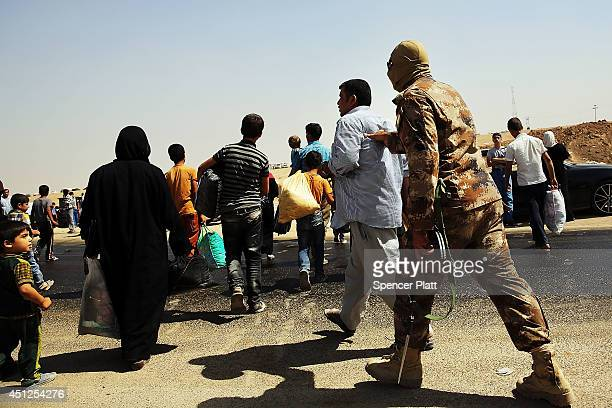 A member of the peshmerga pushes back Iraqi's trying to get into a temporary displacement camp for Iraqis caughtup in the fighting in and around the...