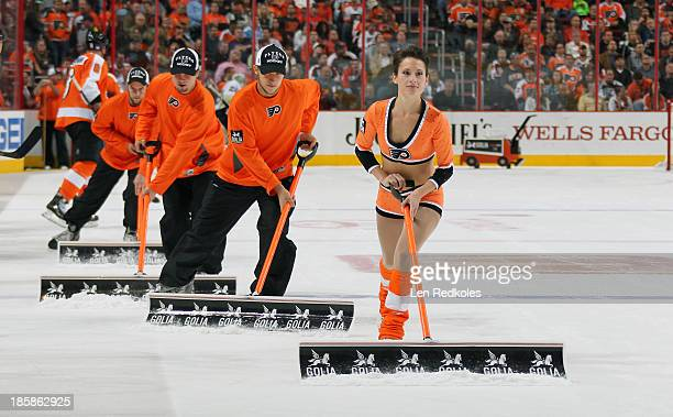 A member of the Philadelphia Flyers ice girls along with the ice crew cleans the ice during a stoppage in play against the Pittsburgh Penguins on...