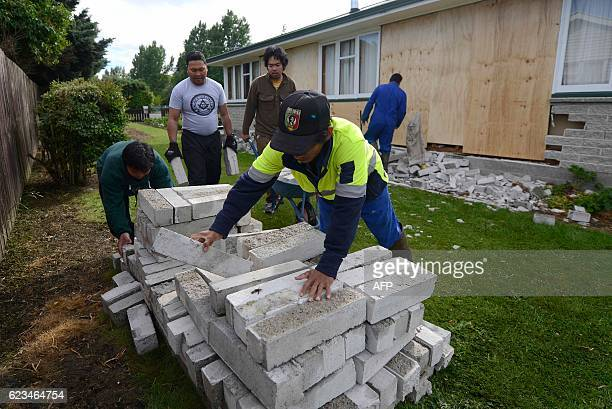 Member of the Philippines community service help to clear damage from a house in Waiau town some 80 kms to the south of Kaikoura on November 16 after...