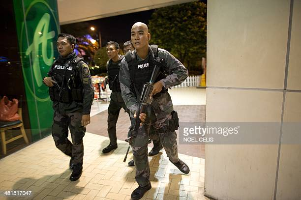 A member of the Philippines police special weapons and tactics unit holds an assault rifle outside one of the world's largest shopping malls...