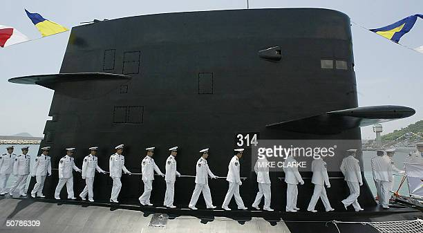 A member of the PLA Navy Task group disembarks from a Chinese PLA Naval submarine berthed in Hong Kong waters 30 April 2004 The submarine was part of...