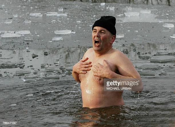 A member of the Polar Wolfs club goes skinny dipping in the ice cold water in a lake near the eastern German town of Zehdenick 26 December 2007 AFP...