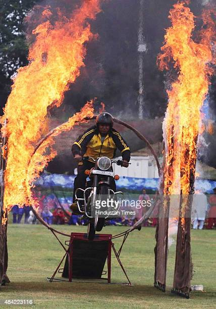 A member of the Police Motor Daredevil team performs a motorcycle stunt through a burning ring during Independence Day celebrations on August 15 2015...