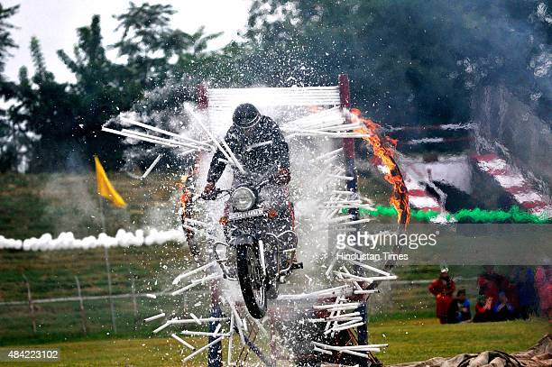 A member of the Police Motorcycle Daredevil team performs a motorcycle stunt during Independence Day celebrations on August 15 2015 in Srinagar India...