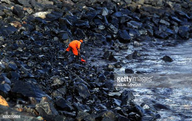 TOPSHOT A member of the Pollution Response Team collects a sample of an oil spill from boulders at the coast a day after an oil tanker and an LPG...