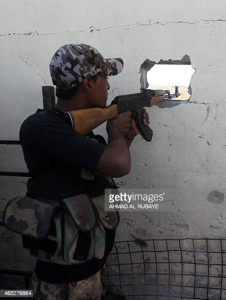 A member of the Popular Mobilisation unit monitors from his position in the village of Awja on the outskirts of the city of Tikrit on March 5...