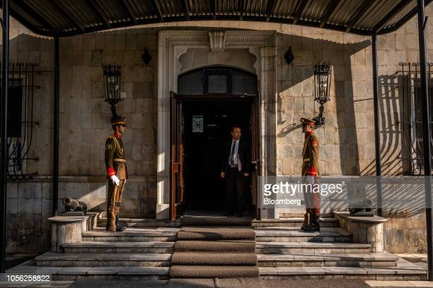A member of the President Protective Service center stands at a door flanked by Presidential Guards at the Presidential Palace in Kabul Afghanistan...