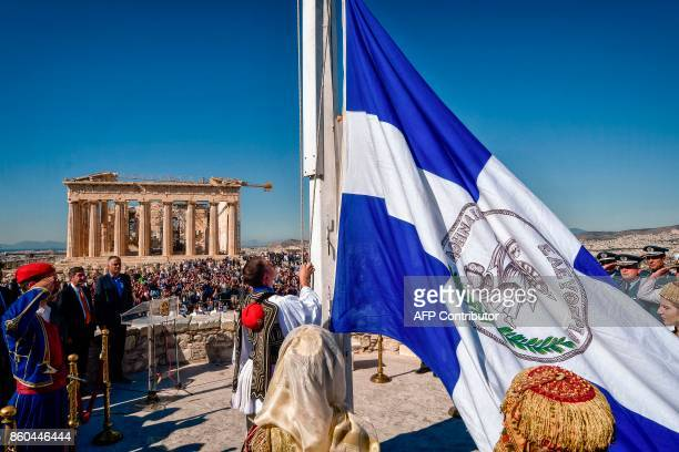 A member of the presidental evzoni guards hoists a greek flag atop the Acropolis hill by the Parthenon temple during a ceremony marking the...