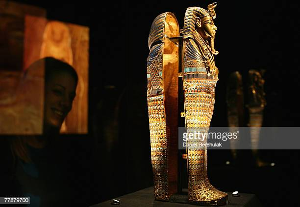 A member of the press observes the Coffinette for the Viscera of Tutankhamun exhibit during the press viewing of 'Tutankhamun The Golden Age of the...