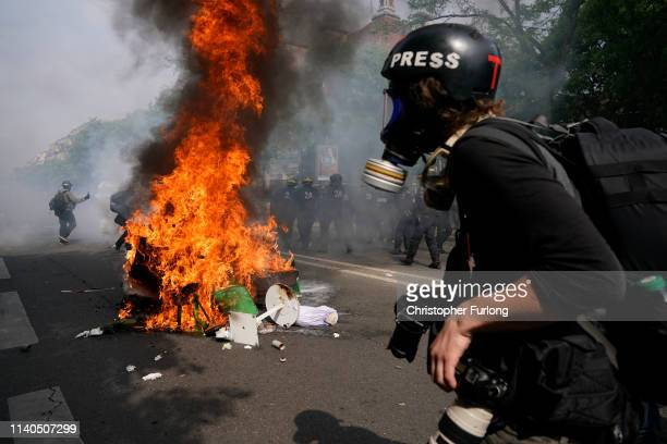 A member of the press walks past burning debris as demonstrators take part in the annual May Day protests on May 01 2019 at 9 Boulevard SaintMarcel...